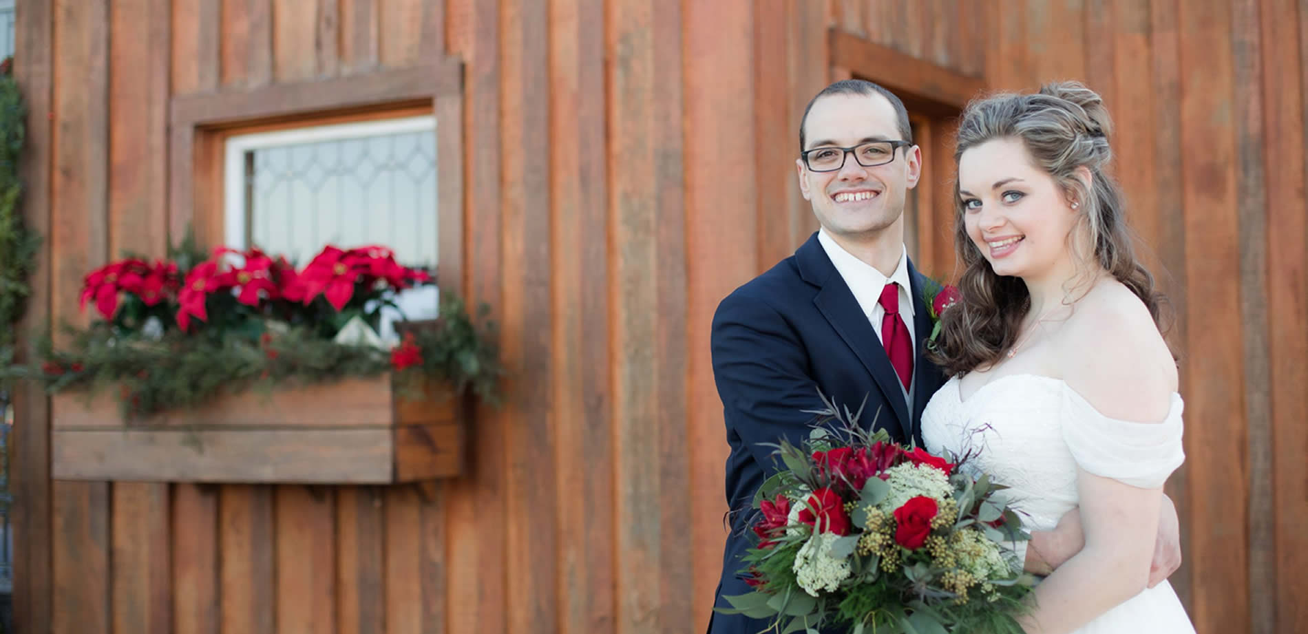 southern grace wedding couple in front of barn